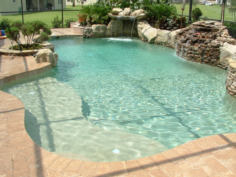 Orlando Pools By Design custom_lagoon_style_freeform_pool_with_sunshelf_natural_stone_and_pebble_interior custom_pool_and_spa_with_stone_waterfall_and_dark_pebble_interior Custom_lagoon_style_freeform_pool_with_sunshelf_natural_stone_and_pebble_interior Custom_pool_and_spa_with_stone_waterfall_and_dark_pebble_interior