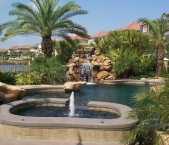 Custom_pool_and_spa_with_stone_waterfall_and_dark_pebble_interior
