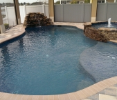 Freeform-pool-with-tanning-ledge-waterfall-paver-deck-stacked-stone-spa-and-dark-blue-pebble-interior
