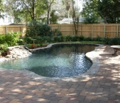 Freeform_lagoon_style_with_natural_stone_waterfall_stone_coping_paver_deck_and_black_pebble_interior
