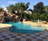 Freeform_pool_raised_spa_large_grotto_with_waterfall_and_slide_travertine_deck_and_coping