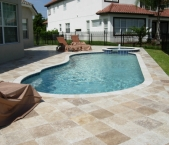 Freeform_pool_with_raised_spa_travertine_coping_and_deck