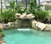 Swimming_oasis__with_swim_thru_rock_grotto_bench__boulder_coping