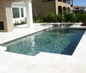 Contemporary_classic_pool_design_spa_sunshelf_with_bubblers_travertine_deck_travertine_coping_and_tahoe_pebble_interior