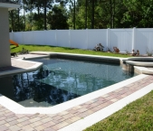 Custom_pool_raised_spa_acrylic_band_with_paver_deck_and_dark_interior_finish